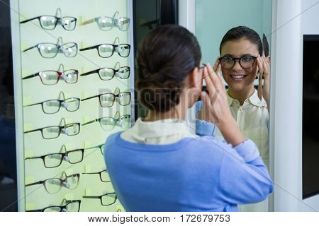 Female customer wearing spectacles and checking in mirror at optical store