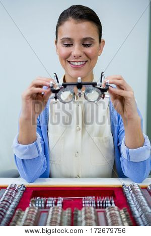 Optician looking at trial frame in optical store