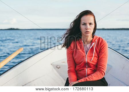 amazing beautiful haired girl swims on a wooden boat and rowing with oars in the gorgeous spring lake. Lifestyle without makeup.