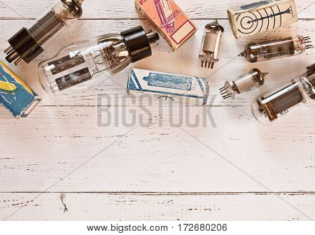 Top view of different tipes of electronic vacuum tubes and packaging them on white wooden background in warm colors.