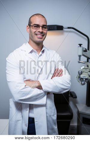 Portrait of male optometrist with arms crossed in ophthalmology clinic