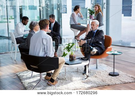 Business executive interacting with each other in office