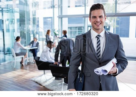 Portrait of smiling businessman standing with document in office