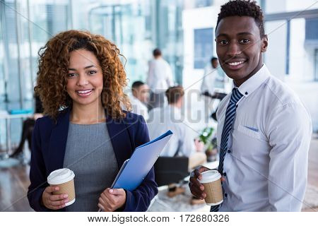 Portrait of smiling business colleagues having coffee in office