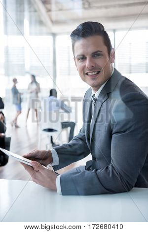 Portrait of smiling businessman using digital tablet in the office