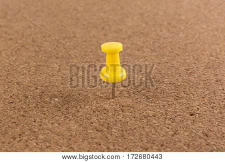 yellow pin on Cork board texture background.