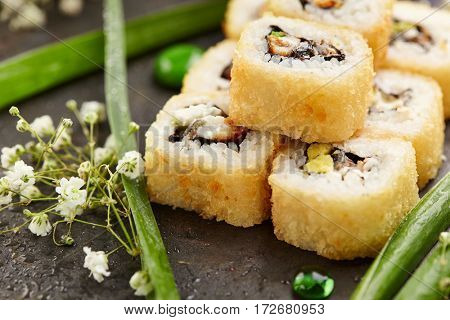 Tempura Maki Sushi - Deep Fried Sushi Roll made of Smoked Eel, Avocado and Cream Cheese inside. Japanese Sushi Food and Natural Flower Concept