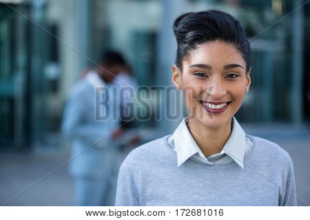 Portrait of smiling businesswoman standing in office building