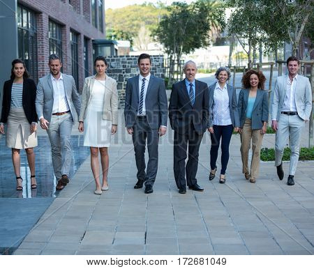 Portrait of smiling businesspeople walking in office building