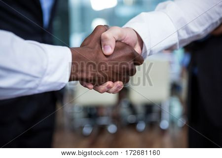 Close-up of businessman shaking hands with colleague in office