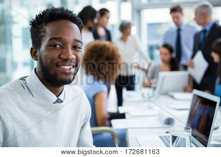 Portrait of smiling businessman sitting in office
