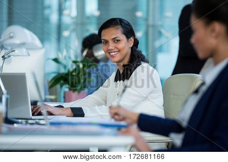 Portrait of smiling businesswoman working on laptop in office
