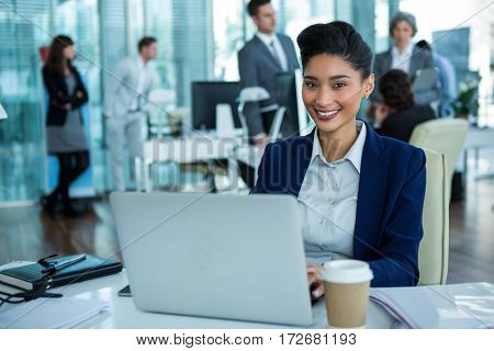Portrait of businesswoman working on laptop in the office