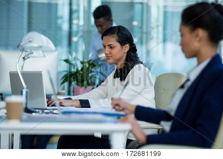 Attentive businesswoman working on laptop in office