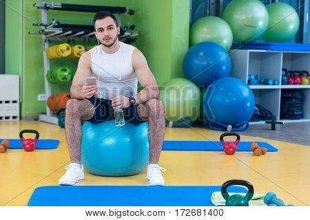 man sitting on a gym ball holding a phone after doing a work out.