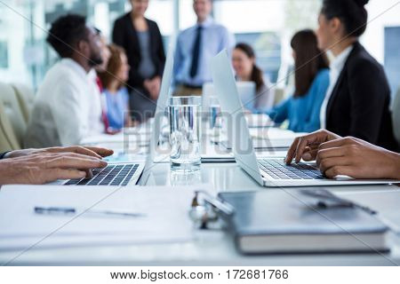 Businesspeople working on laptop in office