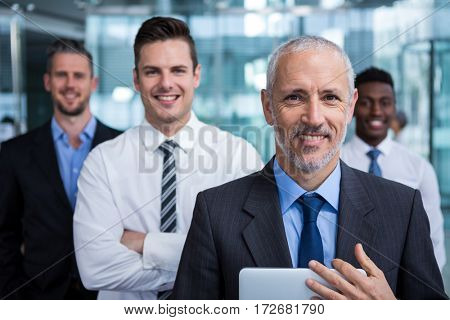 Portrait of happy businessmen standing in office