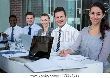 Portrait of happy businesspeople sitting in conference room