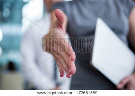 Mid section of businesswoman shaking hand in office