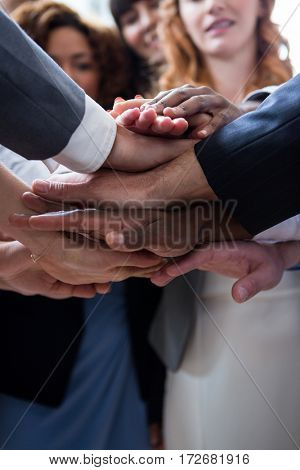 Mid section of businesspeople with hand stacked in office