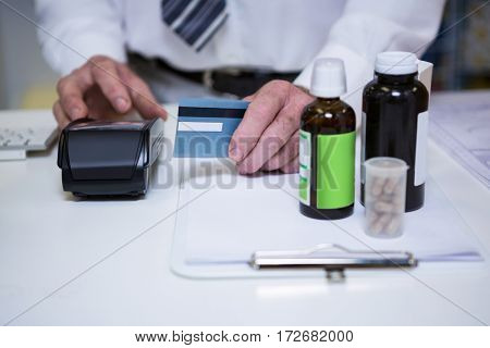 Pharmacist using payment terminal machine at pharmacy