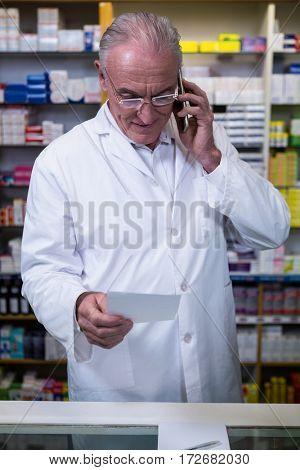 Pharmacist talking on mobile phone while checking prescription in pharmacy