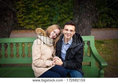 Young Boy And Girl Hugging And Kissing, Sitting On The Bench