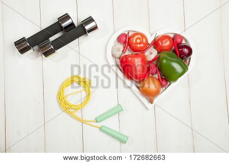Sport and diet. Healthy lifestyle. Vegetables dumbbells. Peppers tomatoes garlic onion and radish in a heart on a white background