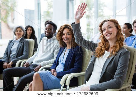 Businesswoman raising hand during meeting in office