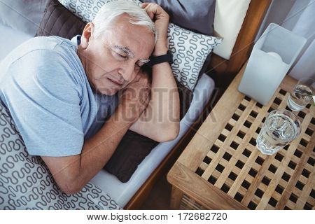 Senior man sleeping on bed at bedroom