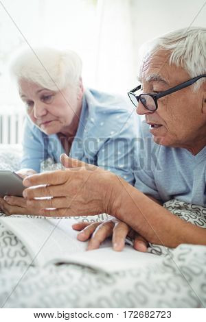 Senior couple interacting with each other on bed at bedroom