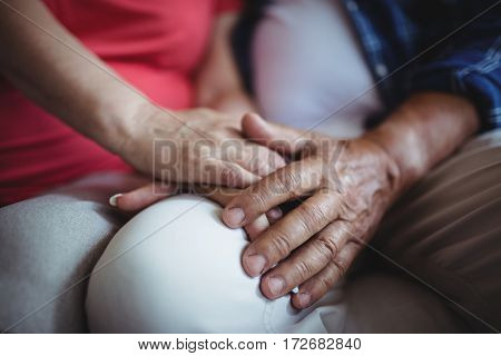 Mid-section of senior couple holding hands at home