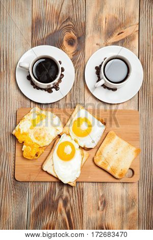 Two Cups With Coffee, Toast And Eggs On A Wooden Table