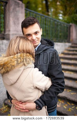 Young Girl And A Guy Are Walking Through The Park, Hugging And Kissing. Romantic Mood