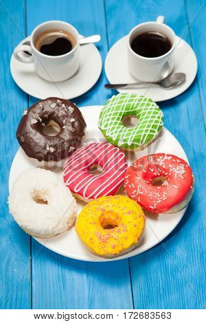 Colorful Donuts And Two Cups Of Coffee On Blue Table