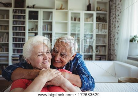 Senior couple embracing each other at home