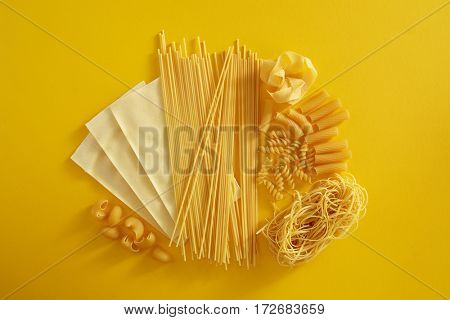 Assorted types of pasta on yellow background. Various forms of pasta, spaghetti, lasagna sheets, fusilli and other.