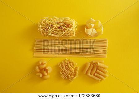 Assorted types of pasta on yellow background. Various forms of pasta.