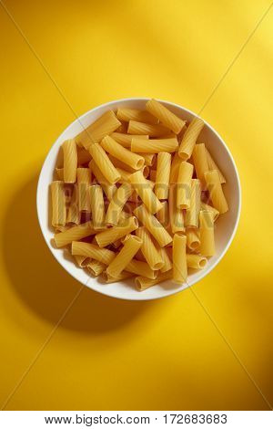 White bowl of dry uncooked pasta on yellow background.