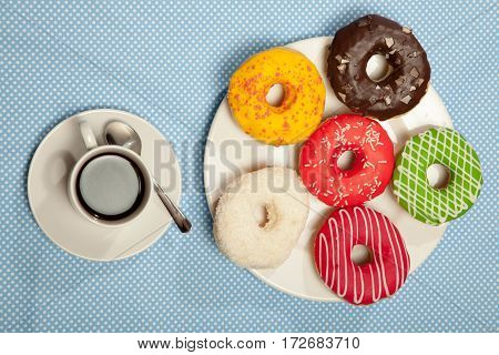 Colorful Donuts And Cups Of Coffee On Blue Table
