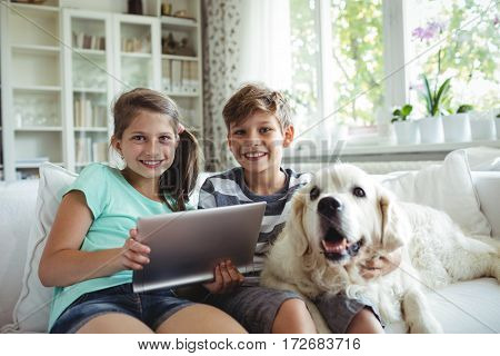 Children using digital tablet while sitting on a sofa at home