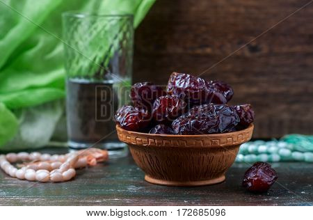 Dates Fruit And Rosary Still Life, On A Dark Wooden Background.