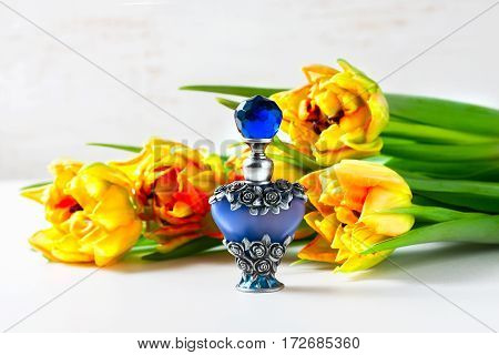 Luxurious Perfume Bottle With Flowers On White Background. Feminine Beauty Concept.