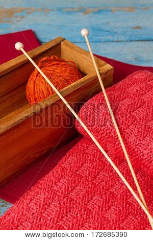 Skein of wool and knitted scarf with spokes on an old wooden table
