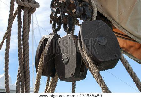 Closeup of three wood pulleys from a sailboat