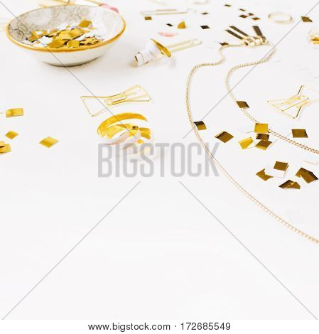 Beauty blog background. Gold style feminine accessories. Golden tinsel pen rings on white background. Top view.