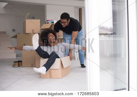 African American couple sitting in a box playing with packing material, having fun after moving in new home