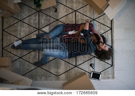 Top view of attractive young multiethnic couple moving, holding hands, looking at camera and smiling while lying among cardboard boxes