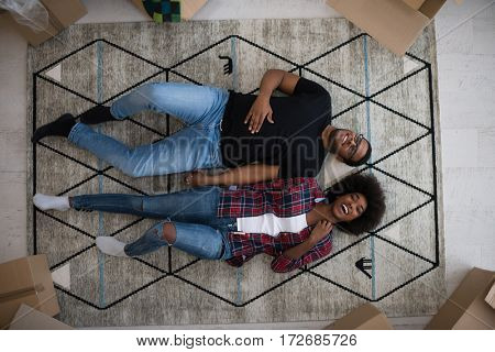 Top view of attractive young African American couple moving, holding hands, looking at camera and smiling while lying among cardboard boxes