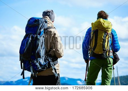 two hikers with backpack on the trail in the Carpathians mountains at winter. hikers stands on the cloudy sky background